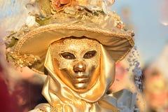 Femme masquée costumée d'or Photographie stock