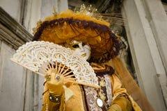 Femme masquée costumée d'or Photographie stock libre de droits