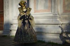 Femme masquée costumée d'or noire Image stock