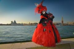 Femme masquée costumée noire et rouge Image libre de droits