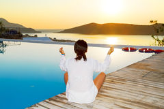 Femme méditant au lever de soleil Photographie stock