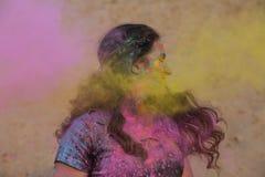 Femme merveilleuse de brune appréciant le festival de Holi au désert Femme posant avec éclater la peinture rose images stock