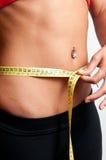 Femme mesurant sa taille Image libre de droits