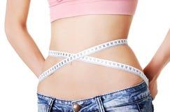 Femme mesurant sa taille Photos stock
