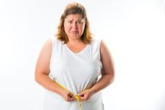 Femme mesurant sa taille avec la bande Photos libres de droits