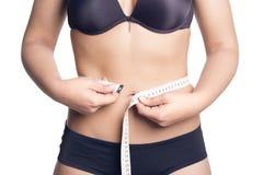 Femme mesurant sa taille avec une bande de mesure Photographie stock libre de droits