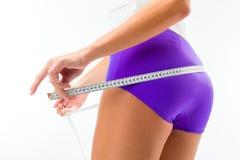 Femme mesurant son gratte-cul avec la bande images stock