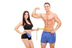 Femme mesurant un athlète masculin bel Image stock