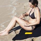 Femme mettant de la lotion dessus Photographie stock libre de droits