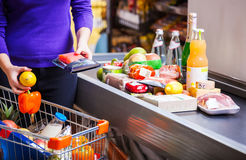 Femme mettant des marchandises sur le compteur dans le supermarché images stock