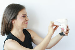 Femme mettant des pièces de monnaie dans son moneybox Images stock