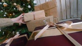 Femme mettant des présents sous l'arbre de Noël banque de vidéos