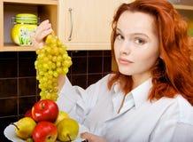 Femme mettant des raisins Photos stock