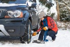 Femme mettant des réseaux de neige sur le pneu du véhicule Photographie stock libre de droits