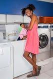 Femme mettant des vêtements dans la machine à laver images libres de droits