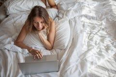 Femme mettant en oeuvre le matin et à l'aide de l'ordinateur portable photo libre de droits
