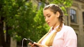 Femme mettant en rouleau les réseaux sociaux utilisant le téléphone, nouvelle demande de téléchargement de musique images stock