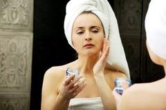 Femme mettant la crème anti-vieillissement sur son visage Image stock