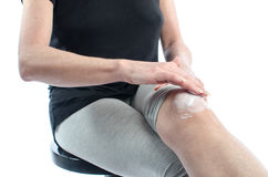 Femme mettant la crème sur son genou Images libres de droits