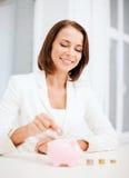 Femme mettant la pièce de monnaie dans la tirelire Photographie stock libre de droits