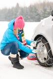 Femme mettant la roue de véhicule de chaînes pour pneumatiques de l'hiver photo stock