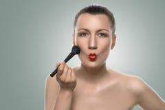 Femme mettant le maquillage sur le visage avec les lèvres boudantes Photo libre de droits