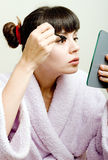 Femme mettant le mascara noir Photos stock