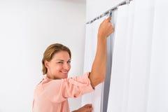 Femme mettant le rideau photo stock