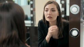 Femme mettant le rouge à lèvres regardant dans le miroir Maquillage la nuit étant prêt avant d'aller faire la fête banque de vidéos