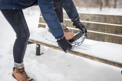Femme mettant non le crampon de neige de glissement sur augmenter la botte en hiver image stock