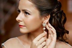 Femme mettant sur des boucles d'oreille de diamant caucasien Photos stock