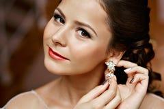 Femme mettant sur des boucles d'oreille de diamant caucasien Photos libres de droits