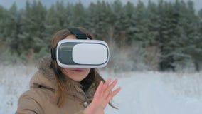 Femme mettant sur et employant des verres de réalité virtuelle dans la forêt d'hiver