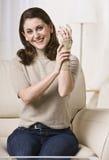 Femme mettant sur le support de poignet Photos stock