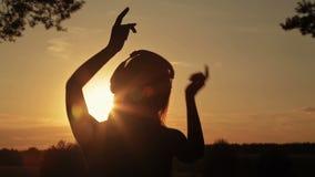 Femme mettant sur les écouteurs, écoutant la musique et dansant dans la forêt clips vidéos