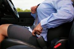 Femme mettant sur sa ceinture de sécurité Photographie stock