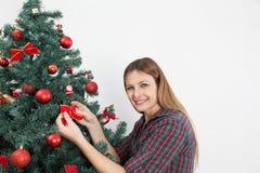 Femme mettant un arc dans l'arbre de Noël Images stock
