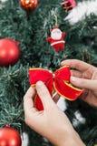 Femme mettant un arc dans l'arbre de Noël Photo libre de droits