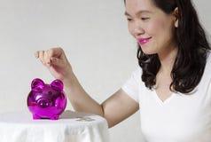 Femme mettant une pièce de monnaie dans la tirelire Photo stock