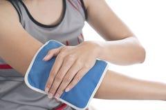 Femme mettant une vessie de glace sur sa douleur de coude Photos stock
