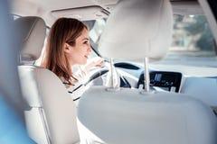 Femme mignonne concentrée s'asseyant dans la voiture et regardant de côté Photos libres de droits