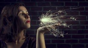 Femme mignonne de brune soufflant la lumière de Bengale Photos stock