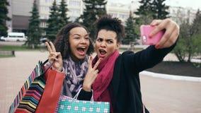 Femme mignonne de l'afro-américain deux prenant le selfie avec des paniers et le sourire Les amis ont l'amusement après vente de  Image stock