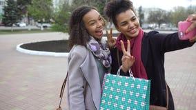 Femme mignonne de l'afro-américain deux prenant le selfie avec des paniers et le sourire Les amis ont l'amusement après vente de  Images libres de droits