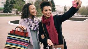 Femme mignonne de l'afro-américain deux prenant le selfie avec des paniers et le sourire Les amis ont l'amusement après vente de  Photos stock