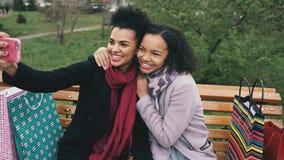 Femme mignonne de l'afro-américain deux prenant le selfie sur le smartphone avec des paniers et le sourire Amies s'asseyant dessu Images libres de droits