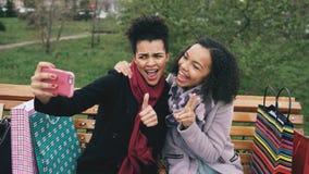Femme mignonne de l'afro-américain deux prenant le selfie sur le smartphone avec des paniers et le sourire Amies s'asseyant dessu Photo libre de droits