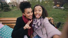 Femme mignonne de l'afro-américain deux prenant le selfie sur le smartphone avec des paniers et le sourire Amies s'asseyant dessu Photo stock