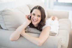 Femme mignonne de sourire se trouvant sur un divan confortable ayant un appel téléphonique Image libre de droits