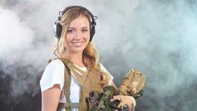 Femme mignonne de tireur isolé avec le fusil dans des mains se tenant dans l'équipement militaire dans l'obscurité Mouvement lent banque de vidéos